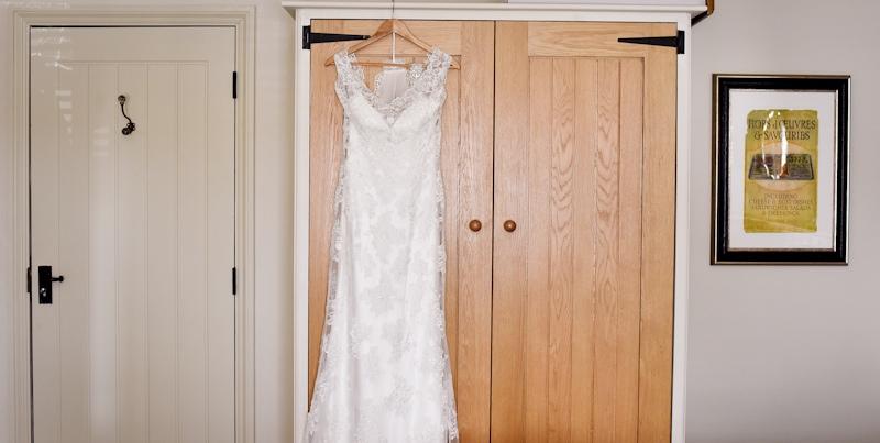 photograph of brides wedding dress on wardrobe