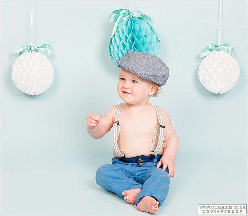 baby boy, flat cap, braces, professional photograph,