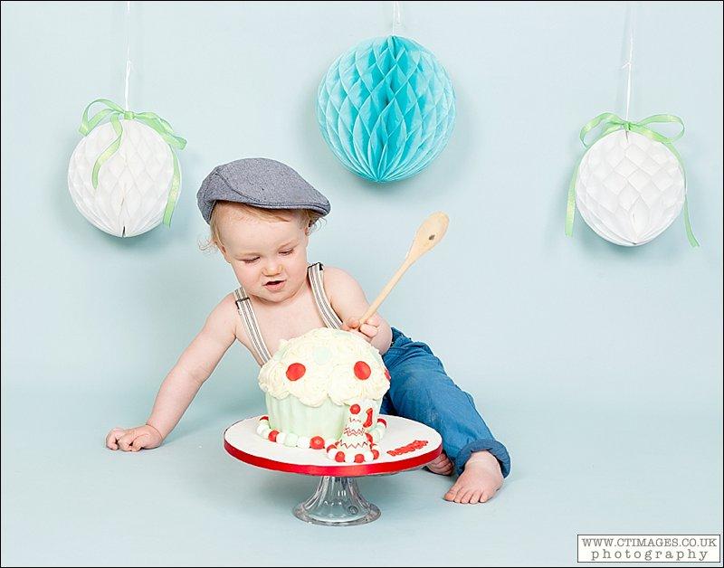 baby boy cake smash, flat cap, wooden spoon, boy in braces,