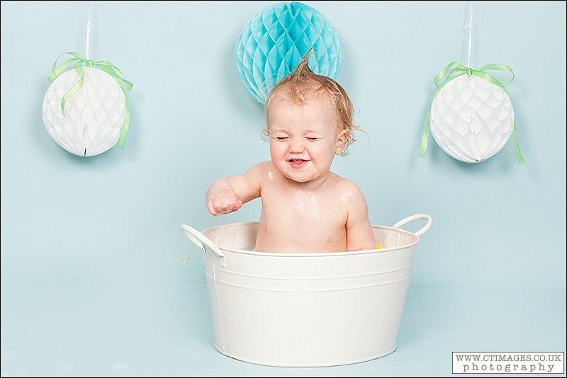 baby in bath tub, baby boy, blue backdrop, baby laughing in bath,